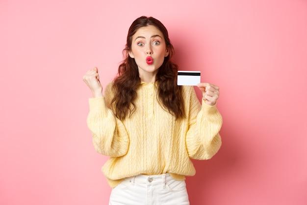 Podekscytowana kupująca dziewczyna mówi tak, robi pompkę pięścią i wygląda na zdumioną, pokazując plastikową kartę kredytową i gotowa do zakupów, stojąc przed różową ścianą.