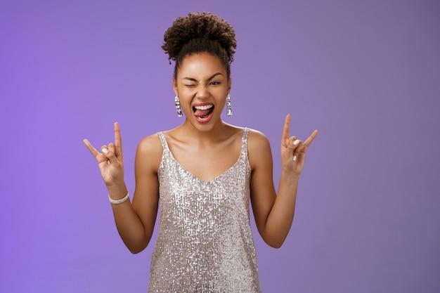 Podekscytowana, ładna afroamerykanka w błyszczącej srebrnej błyszczącej sukience bawi się zabawnie na uniwersyteckiej imprezie balowej, pokazuje język, mrugając radośnie, rock-n-roll, heavy-metalowy gest, niebieska ściana.