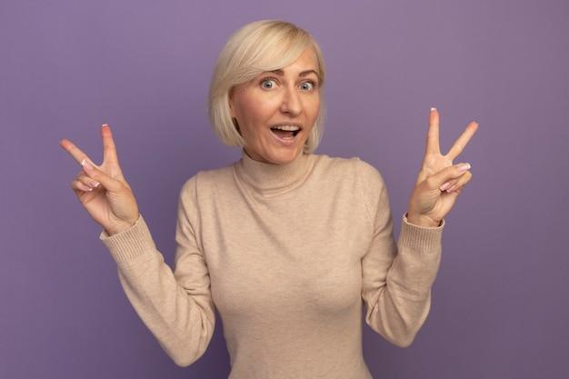 Podekscytowana ładna blondynka słowiańska gestykuluje ręką znak zwycięstwa dwiema rękami na fioletowo