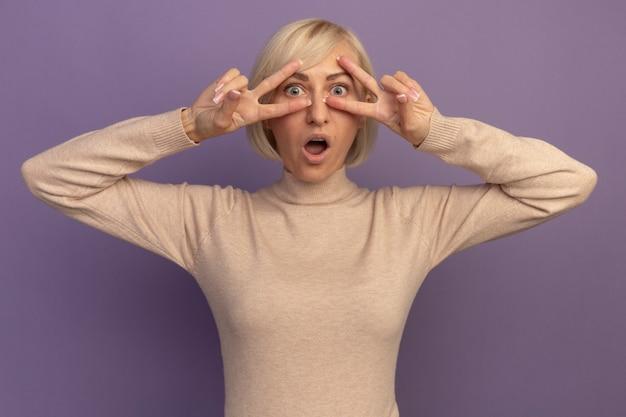 Podekscytowana ładna blondynka słowiańska gestykuluje ręką znak zwycięstwa dwiema rękami patrząc na kamery