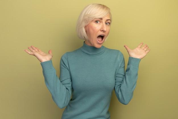 Podekscytowana ładna blondynka słowiańska kobieta stoi z podniesionymi rękami na oliwkowej zieleni