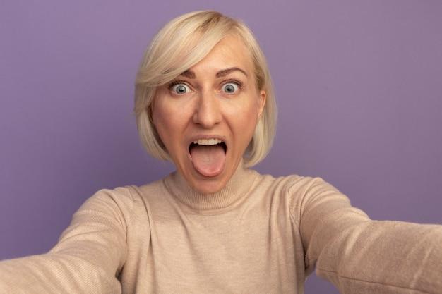 Podekscytowana ładna blondynka słowiańska kobieta wystawia język i udaje, że trzyma aparat na fioletowo