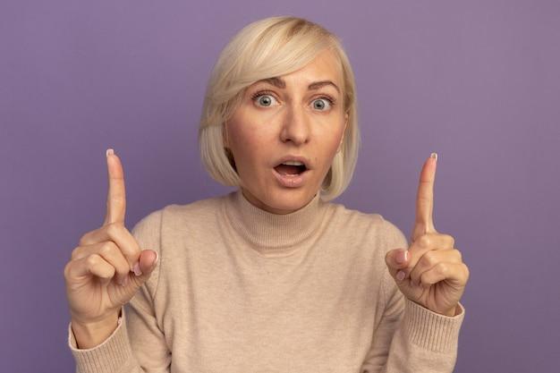 Podekscytowana ładna blondynka słowiańska wskazuje dwiema rękami na fioletowo