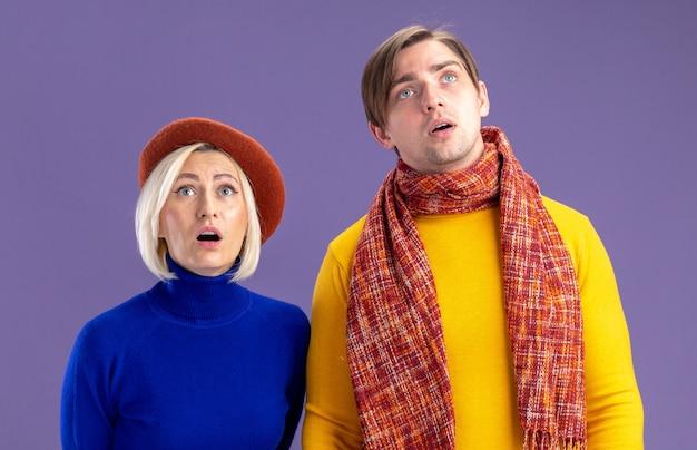 Podekscytowana ładna blondynka z beretem i przystojnym słowiańskim mężczyzną z szalikiem na szyi, patrząc na odizolowaną na fioletowej ścianie z miejscem na kopię