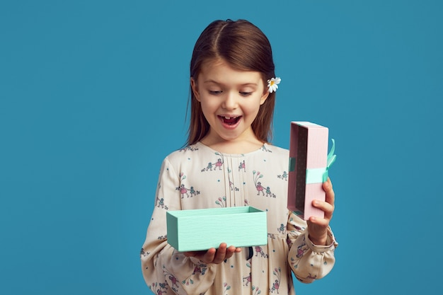 Podekscytowana ładna dziewczyna trzyma otwarte pudełko na prezent na białym tle nad niebieską ścianą