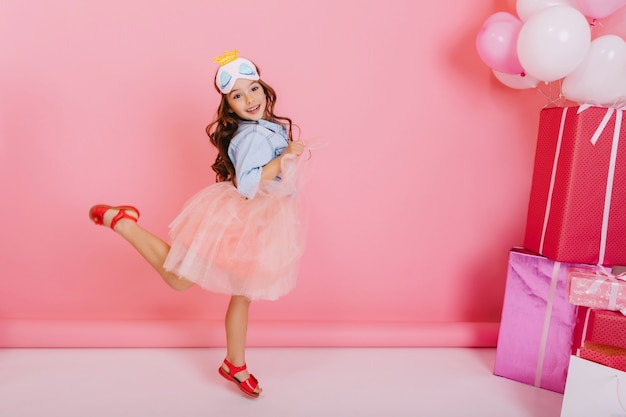 Podekscytowana ładna dziewczyna urodziny z długimi włosami brunetki, w tiulowej spódnicy, skoki, zabawy na białym tle na różowym tle. jasne świętowanie niesamowitego szczęśliwego dzieciaka z pudełkami, balonami