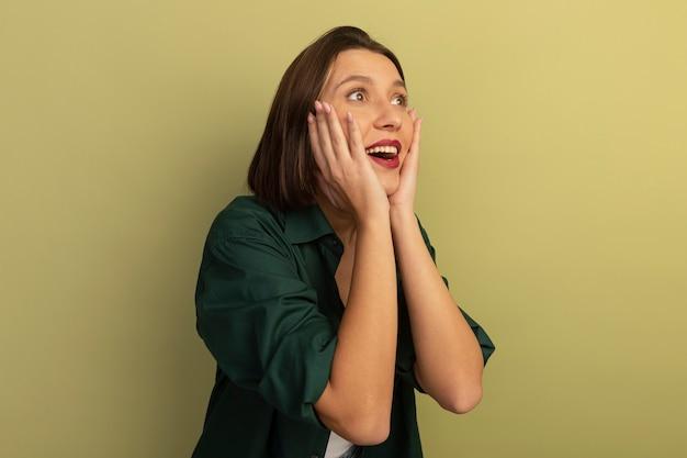 Podekscytowana ładna kaukaska kobieta kładzie ręce na twarzy i patrzy z boku na oliwkową zieleń