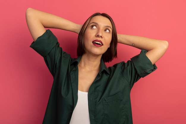 Podekscytowana ładna kobieta kładzie ręce na głowie za i patrzy w górę na białym tle na różowej ścianie