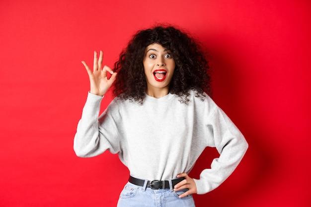 Podekscytowana ładna kobieta mówi tak, pokazuje dobry gest i wygląda entuzjastycznie, zgadza się lub lubi coś, robi komplement, stoi na czerwonej ścianie