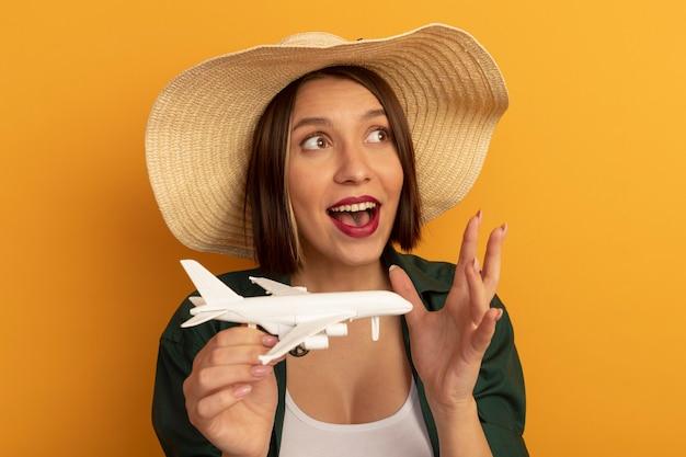 Podekscytowana ładna kobieta w kapeluszu plażowym trzyma model samolotu i patrzy na bok na białym tle na pomarańczowej ścianie