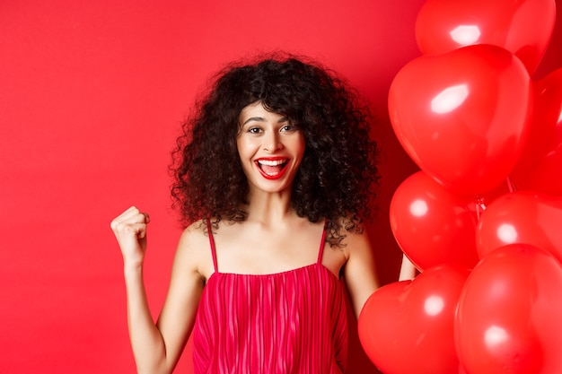Podekscytowana ładna kobieta wygrywająca, mówi tak i uśmiecha się, świętuje sukces, motywuje pompkę pięścią, stoi w pobliżu balonów serca i czerwonego tła.