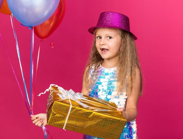 Podekscytowana mała blondynka w fioletowym kapeluszu imprezowym trzymająca balony z helem i pudełko na prezenty odizolowane na różowej ścianie z miejscem na kopię
