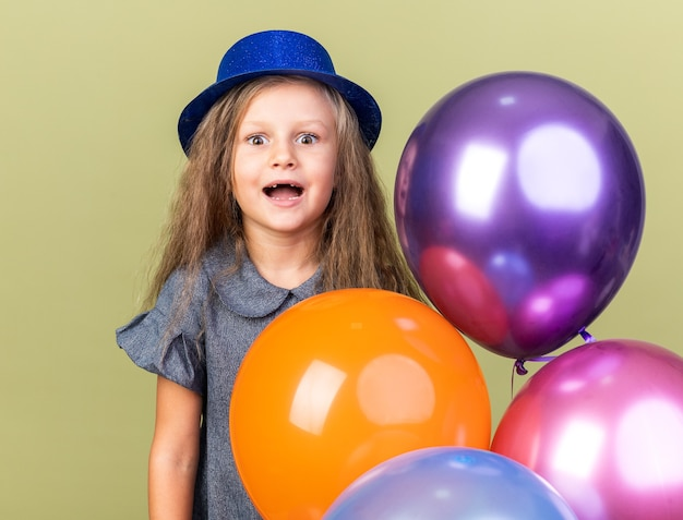 Podekscytowana mała blondynka z niebieskim kapeluszem strony, trzymając balony z helem na białym tle na oliwkowej ścianie z miejsca na kopię