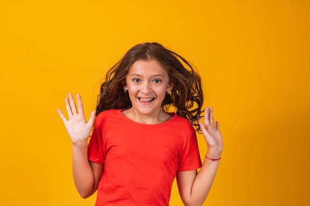Podekscytowana mała dziewczynka skoki na żółtym tle. ekspresyjna dziewczyna zszokowana na żółtym tle.