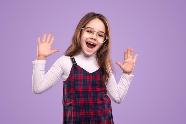 Podekscytowana mała kujonka w szkolnym mundurku i okularach, bawiąca się i pokazująca dziesięć palców stojąc na fioletowym tle