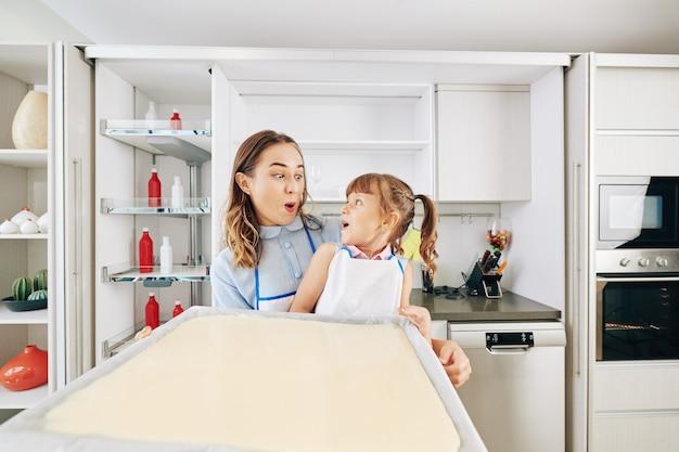 Podekscytowana mama i córka patrzą na siebie podczas wkładania dużej blachy do piekarnika