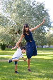 Podekscytowana mama i synek grają w aktywne gry na świeżym powietrzu, stojąc i balansując na jednej nodze, wykonując zabawne ćwiczenia w parku. rodzinna koncepcja aktywności i wypoczynku na świeżym powietrzu