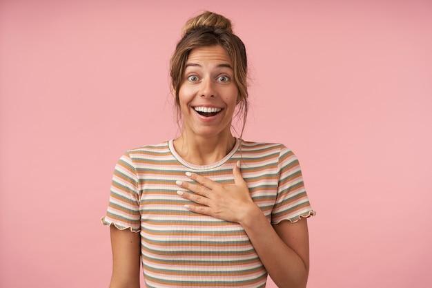 Podekscytowana młoda atrakcyjna brązowowłosa dama unosząca zaskoczone brwi, patrząc radośnie na aparat i trzymając dłoń na piersi, odizolowana na różowym tle