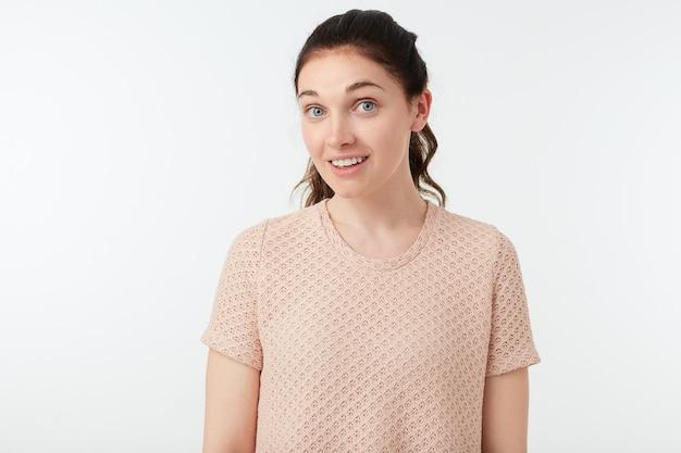 Podekscytowana młoda atrakcyjna brązowowłosa kobieta ubrana w t-shirt nago