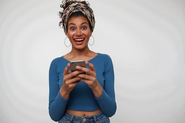 Podekscytowana młoda atrakcyjna ciemnowłosa kręcona kobieta ze smartfonem w uniesionych rękach patrząc podekscytowany na aparat z szerokim uśmiechem stojąc na białym tle