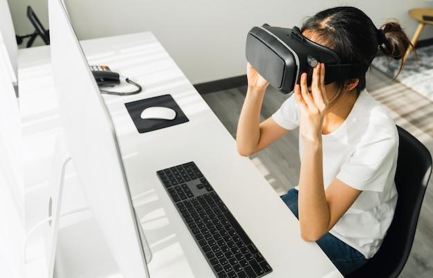 Podekscytowana młoda azjatka korzystająca z zestawu słuchawkowego i joysticków wirtualnej rzeczywistości, połączenia concept i interfejsów technologii cyfrowej.