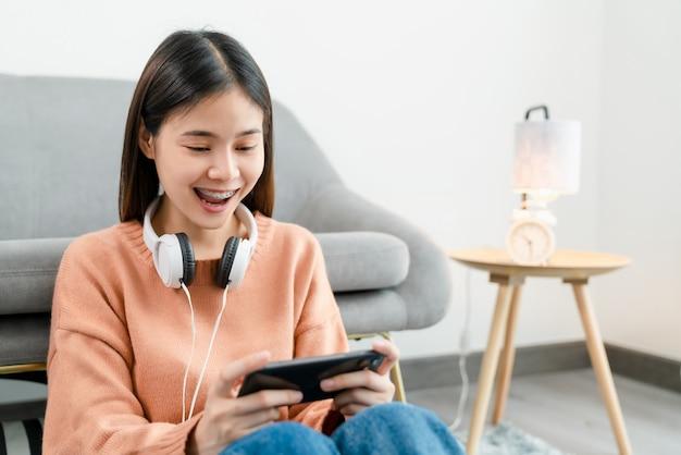 Podekscytowana młoda azjatka nosi białe słuchawki na głowie i grając w gry