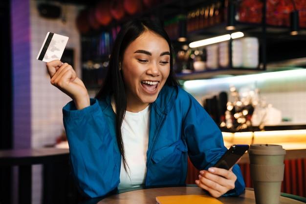 Podekscytowana młoda azjatycka kobieta korzystająca z telefonu komórkowego i trzymająca kartę kredytową siedząc w kawiarni