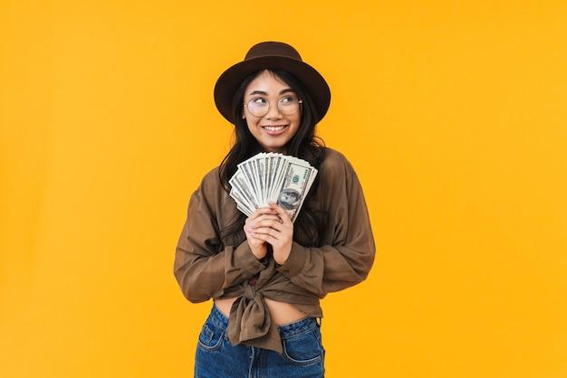 Podekscytowana młoda azjatycka kobieta pokazująca banknoty pieniężne stojąc na żółto