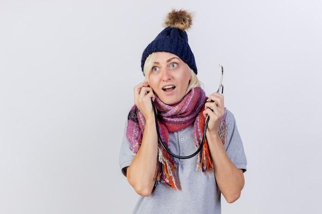 Podekscytowana młoda blondynka chora kobieta w czapce zimowej i szaliku trzyma stetoskop na białym tle na białej ścianie