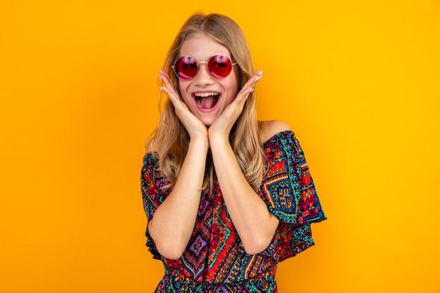 Podekscytowana młoda blondynka słowiańska w okularach przeciwsłonecznych, kładąca ręce na twarzy i patrząca w bok