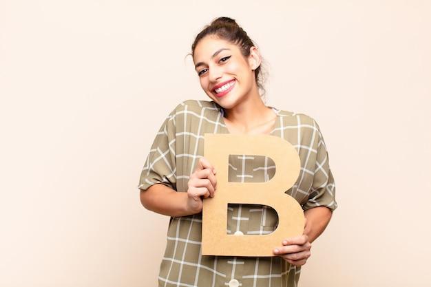 Podekscytowana młoda brunetka kobieta trzyma literę b.