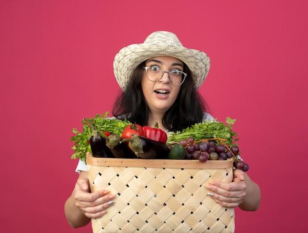 Podekscytowana młoda brunetka ogrodniczka w okularach optycznych iw mundurze na sobie kapelusz ogrodniczy trzyma kosz warzyw na różowej ścianie