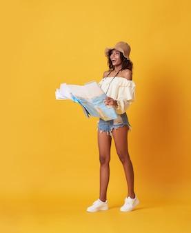 Podekscytowana młoda czarna kobieta, ubrana w letnie ubrania, trzyma mapę podróży i patrzy