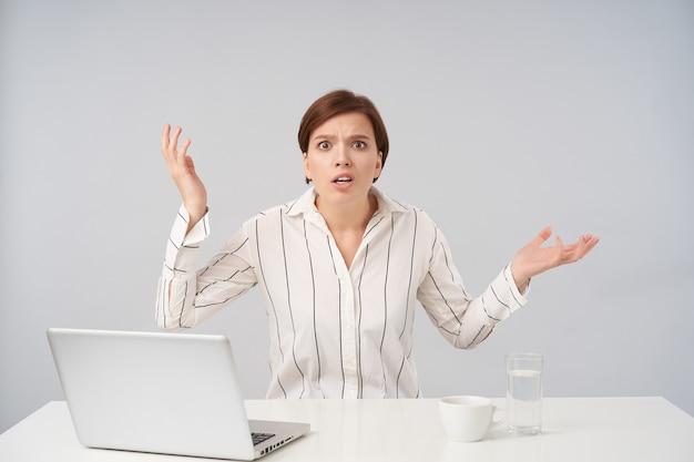 Podekscytowana młoda dość krótkowłosa brunetka kobieta ubrana w białą koszulę w paski z zakłopotaniem zaokrąglająca oczy i unosząca emocjonalnie dłonie w górę, siedząca na białym