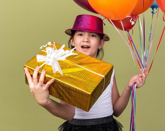 Podekscytowana młoda dziewczyna kaukaska z fioletowym kapeluszem strony trzymającej balony z helem i pudełko na białym tle na oliwkowej ścianie z miejsca na kopię