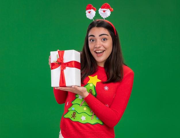 Podekscytowana młoda dziewczyna kaukaski z opaską santa trzyma pudełko na prezent na boże narodzenie na białym tle na zielonym tle z miejsca na kopię