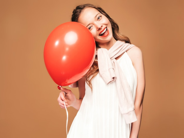 Podekscytowana młoda dziewczyna pozuje w modnej letniej białej sukni. kobieta model z czerwony balonik pozowanie. gotowy na imprezę
