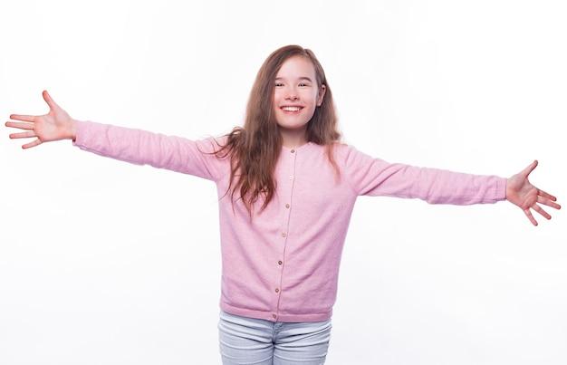 Podekscytowana młoda dziewczyna stoi z szeroko otwartymi ramionami, gotowa do przytulenia.
