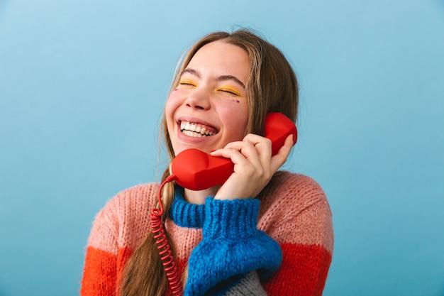 Podekscytowana młoda dziewczyna ubrana w zimowe ubrania stoi na białym tle, rozmawia przez telefon stacjonarny
