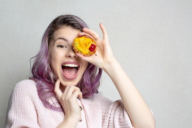 Podekscytowana młoda dziewczyna z fioletowymi włosami zasłaniającymi jej oczy słodkim deserem z owocami. miejsce na tekst