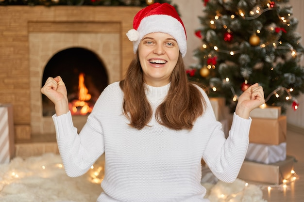 Podekscytowana młoda europejska dziewczyna santa w ciepłym swetrze i świątecznej czapce, obchody szczęśliwego nowego roku, dama zaciskająca pięści jak zwycięzca z radosną miną.
