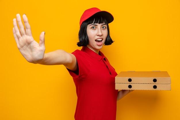 Podekscytowana młoda kaukaska dziewczyna dostarczająca pizzę trzymająca pudełka po pizzy i wyciągająca rękę