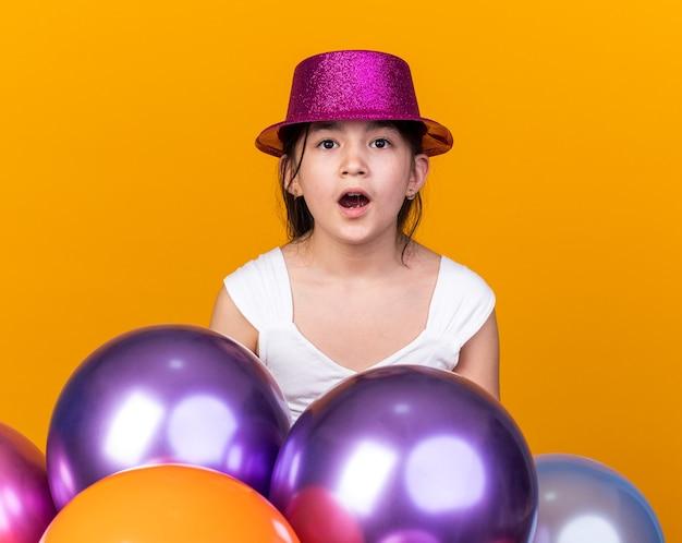 Podekscytowana młoda kaukaska dziewczyna w fioletowym kapeluszu stojącym z balonami z helem na pomarańczowej ścianie z miejscem na kopię