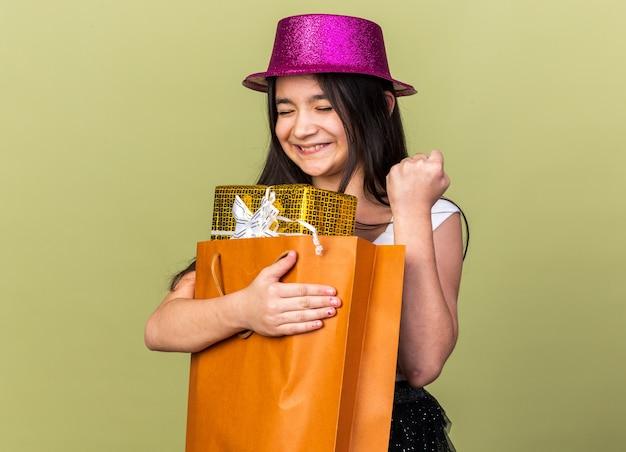 Podekscytowana młoda kaukaska dziewczyna z fioletowym kapeluszem imprezowym trzymająca pudełko w torbie na zakupy i trzymająca pięść odizolowana na oliwkowej ścianie z miejscem na kopię