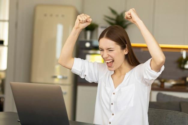 Podekscytowana młoda kobieta kaukaski świętuje osiągnięcie celu marzeń. udana dziewczyna bizneswoman cieszy się z wyników projektu finansowego
