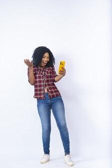 Podekscytowana młoda kobieta korzystająca z telefonu, czując się zaskoczona i szczęśliwa