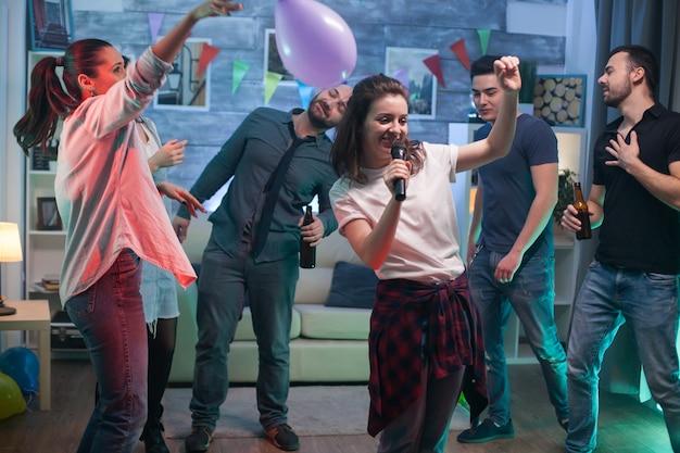 Podekscytowana młoda kobieta na imprezie robi karaoke dla swoich przyjaciół.