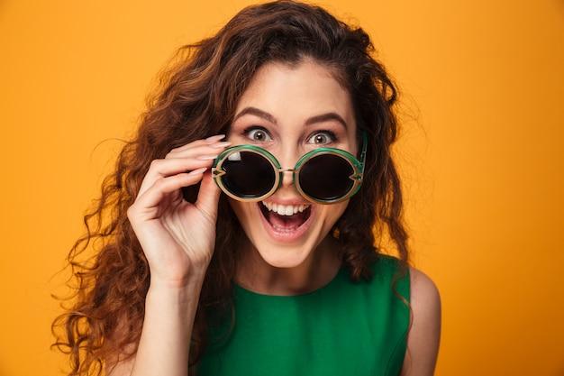 Podekscytowana młoda kobieta nosi okulary przeciwsłoneczne.