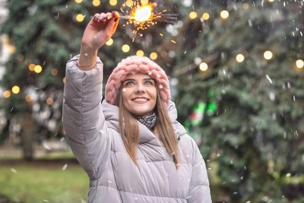 Podekscytowana młoda kobieta nosi różowy dzianinowy kapelusz i płaszcz, bawiąc się ognie na ulicy w pobliżu choinki podczas opadów śniegu