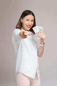 Podekscytowana młoda kobieta odizolowana nad szarą ścianą trzymająca w dłoni pieniądze wskazujące palcem do przodu